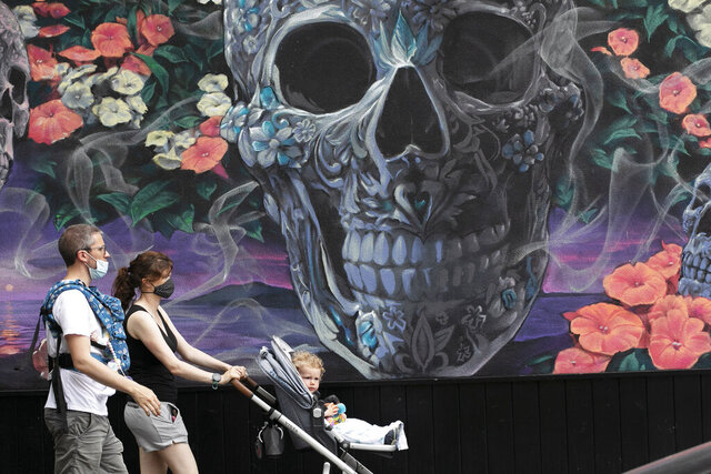 Parents wearing masks walk with their children past a mural, Friday, May 29, 2020, in New York. Gov. Andrew Cuomo says New York City is on track to begin reopening June 8 as the state gradually loosens restrictions put in place during the coronavirus crisis. (AP Photo/Mark Lennihan)