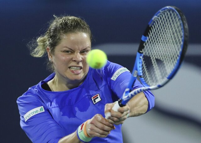 FILE - In this Feb. 17, 2020, file photo, Belgium's Kim Clijsters returns the ball to Spain's Gabrine Muguruza during a match of the Dubai Duty Free Tennis Championship in Dubai, United Arab Emirates. Any World TeamTennis player or coach who tests positive for COVID-19 when arriving for the three-week 2020 season will be dropped from the league without pay. The health plan released Tuesday, June 16, 2020, by the WTT for its matches starting July 12 at The Greenbrier in West Virginia also calls for two daily temperature checks for spectators, no ball kids, a chair umpire aided by electronic line-calling instead of line judges, and no high-fives or handshakes between opponents. The rosters announced for the WTT's nine teams include Grand Slam title winners Kim Clijsters, Sloane Stephens, Sofia Kenin and the Bryan brothers.  (AP Photo/Kamran Jebreili, File)