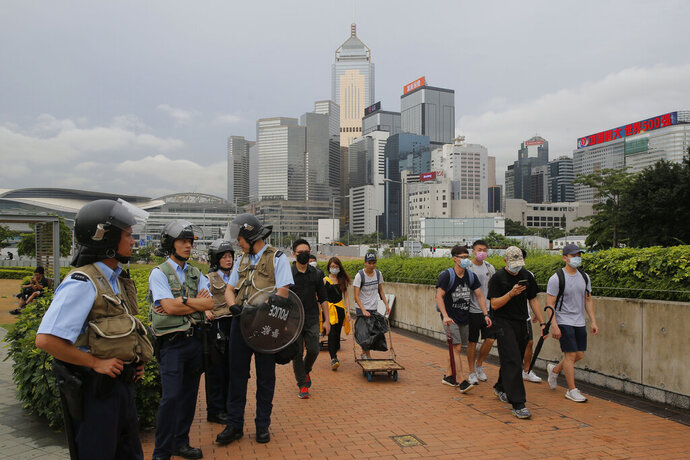 Riot police stand guard as protesters walk outside the Legislative Council in Hong Kong, Thursday, June 13, 2019. After days of silence, Chinese state media is characterizing the largely peaceful demonstrations in Hong Kong as a