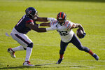 Chicago Bears' David Montgomery is tackled by Houston Texans' Carlos Watkins (91) during the first half of an NFL football game, Sunday, Dec. 13, 2020, in Chicago. (AP Photo/Nam Y. Huh)