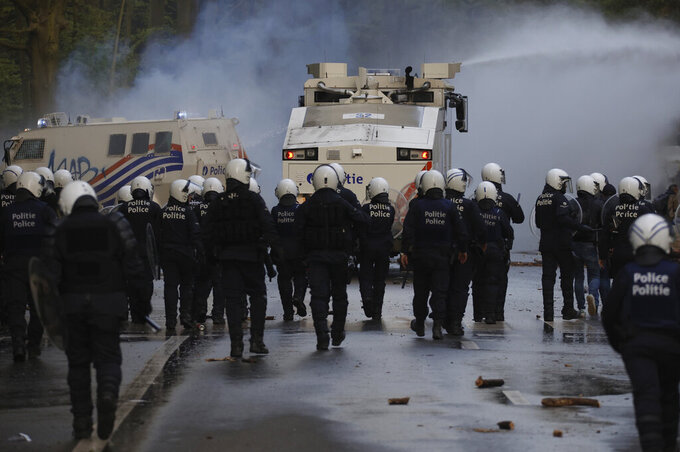 "Police disperse protestors with a water cannon at the Bois de la Cambre park during a party called ""La Boum 2"" in Brussels, Saturday, May 1, 2021. A few thousand people gathered for an illegal party in a Brussels park Saturday to protest COVID-19 restrictions, only to be met with a big police force who used a water cannon and tear gas to disperse the crowd. It was the second such open-air gathering in a month. (AP Photo/Olivier Matthys)"