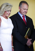 Former Alabama Chief Justice Roy Moore, right, and his wife Kayla pray before a press conference where he announced he is running for the republican nomination for U.S. Senate, Thursday, June 20, 2019, in Montgomery, Ala. (AP Photo/Julie Bennett)