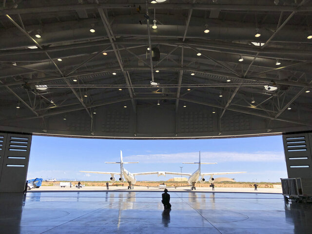 FILE - In this Aug. 15, 2019, file photo, Virgin Galactic ground crew guide the company's carrier plane into the hangar at Spaceport America following a test flight over the desert near Upham, New Mexico. Virgin Galactic has been selected to provide regular access to flights for NASA payloads as the space agency conducts more research and development and plans for exploratory missions. NASA announced the partnership Monday, Nov. 30, 2020. Virgin Galactic is preparing for its first test space flight from Spaceport America in New Mexico. The window for that flight opens Dec. 11. (AP Photo/Susan Montoya Bryan, File)