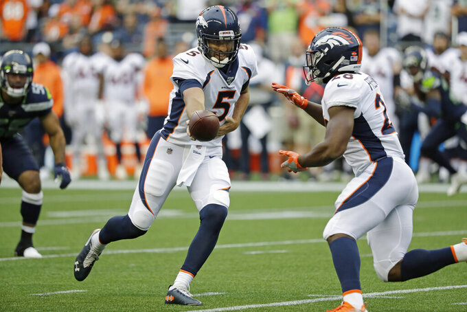 Denver Broncos quarterback Joe Flacco hands off to running back Royce Freeman, right, during the first half of the team's NFL football preseason game against the Seattle Seahawks, Thursday, Aug. 8, 2019, in Seattle. (AP Photo/Elaine Thompson)
