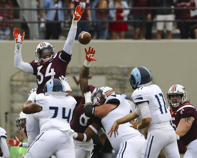Rhode Island quarterback Vito Priore (17) has a pass batted down by Virginia Tech defender Alan Tisdale (34) in the first half of an NCAA college football game in Blacksburg Va., Saturday, Oct. 12 2019. (Matt Gentry/The Roanoke Times via AP)
