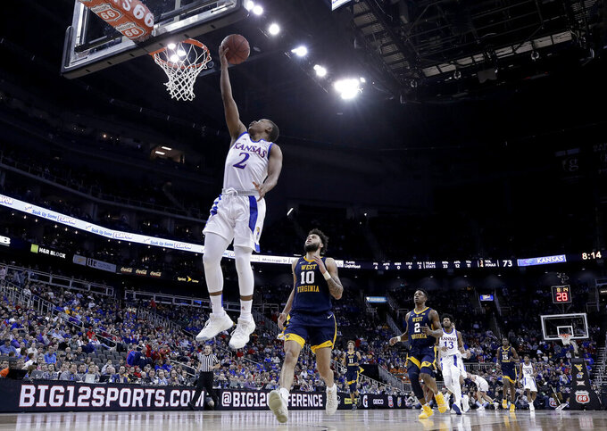 Kansas' Charlie Moore (2) gets past West Virginia's Jermaine Haley for a shot during the second half of an NCAA college basketball game in the Big 12 men's tournament Friday, March 15, 2019, in Kansas City, Mo. Kansas won 88-74. (AP Photo/Charlie Riedel)
