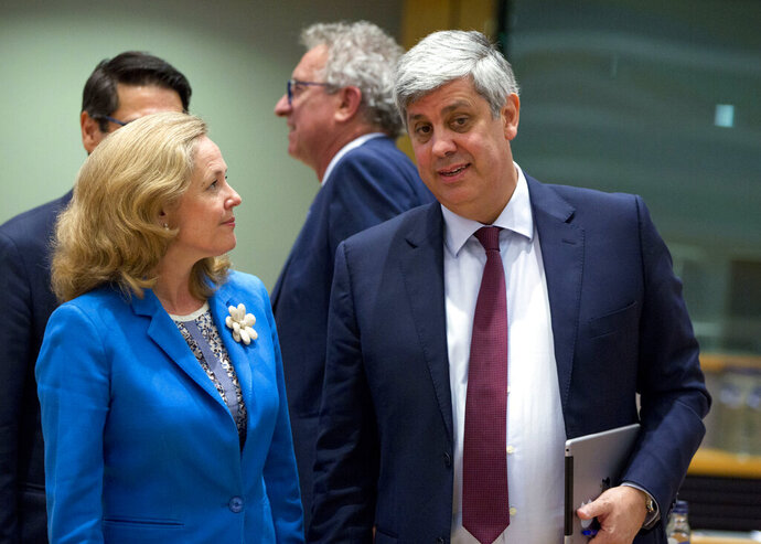 FILE - In this Monday, July 8, 2019 file photo, Spanish Economy Minister Nadia Calvino, left, speaks with President of the eurogroup Mario Centeno during a meeting of the europgroup at the Europa building in Brussels. Spain on Thursday, June 25, 2020 nominated Economy Minister Nadia Calvino as the next head of the 19-nation Eurogroup, one of the EU's most powerful bodies. (AP Photo/Virginia Mayo, File)