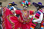 Performers in costume attend a Day of the Dead parade in Mexico City, Sunday, Oct. 27, 2019. The parade on Sunday marks the fourth consecutive year that the city has borrowed props from the opening scene of the James Bond film,