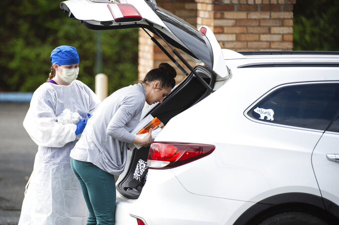 A woman delivers medical supplies at a screening clinic at Hartselle Family Practice, organized by Decatur Morgan Hospital, on Tuesday, March 24, 2020, in Hartselle, Ala. Those who meet the criteria for COVID-19 testing are sent to another site. (Dan Busey/The Decatur Daily via AP)