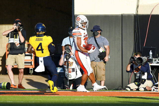 Oklahoma State running back Chuba Hubbard (30) scores a touchdown during the second half of an NCAA college football game against West Virginia Saturday, Sept. 26, 2020, in Stillwater, Okla. (AP Photo/Brody Schmidt)