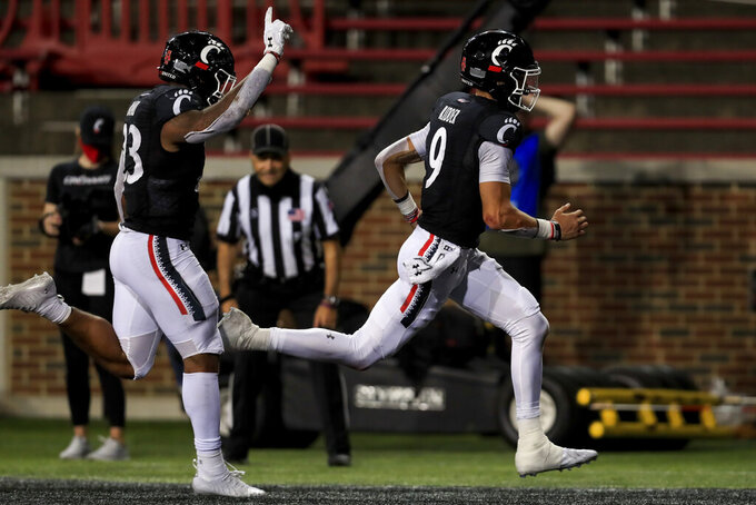 Cincinnati running back Gerrid Doaks, left, reacts as quarterback Desmond Ridder, right, scores a rushing touchdown during the second half of an NCAA college football game against Houston, Saturday, Nov. 7, 2020, in Cincinnati. (AP Photo/Aaron Doster)