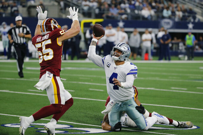 Dallas Cowboys quarterback Dak Prescott (4) is hit by Washington Redskins linebacker Montez Sweat (90) and pressured by linebacker Cole Holcomb (55) as he tires to pass during the first half of an NFL football game in Arlington, Texas, Sunday, Dec. 15, 2019. (AP Photo/Michael Ainsworth)