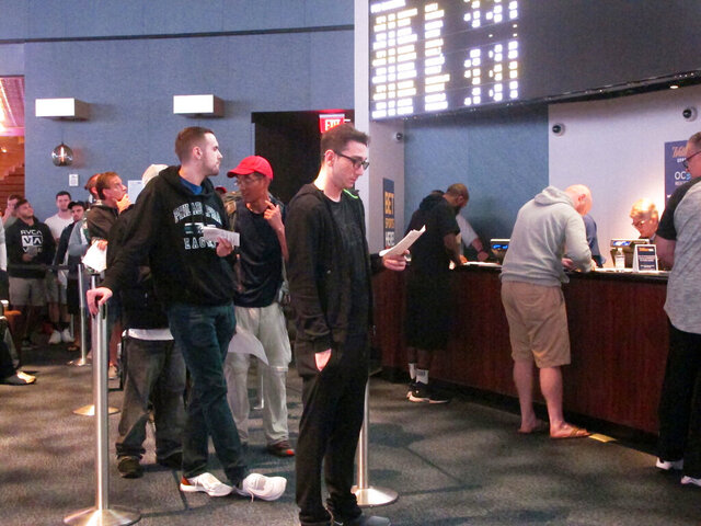 Customers line up to place wagers in the sports betting lounge at the Ocean Resort Casino in Atlantic City N.J. on Sept. 9, 2018. The coronavirus outbreak has added new wrinkles for bettors this year, but even so, the nation's sportsbooks expect a record year of bets on football in 2020 from an antsy public that has been cooped up for months amid the pandemic. (AP Photo/Wayne Parry)