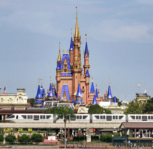 A view of Cinderella Castle from Seven Seas Lagoon in the Magic Kingdom at Walt Disney World, in Lake Buena Vista, Fla., Wednesday, Sept. 30, 2020. The Walt Disney Co. announced Tuesday that it is planning to lay off 28,000 workers in its theme parks division in California and Florida. The company has been squeezed by limits on attendance at its parks and other restrictions due to the pandemic. (Joe Burbank/Orlando Sentinel via AP)