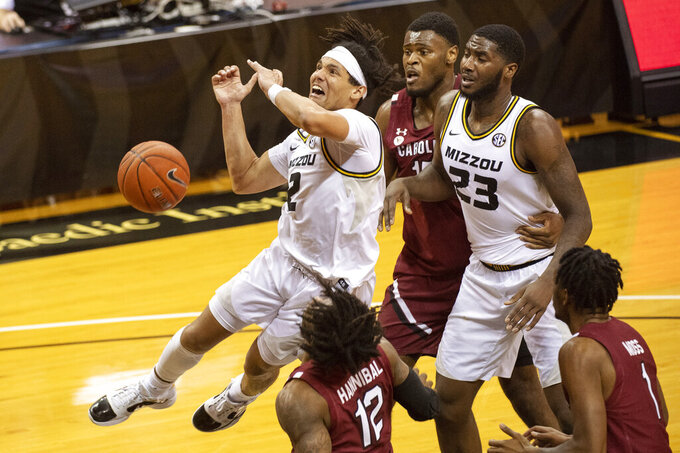 Missouri's Drew Buggs, left, loses control of the ball as he shoots in front of South Carolina's Jeremiah Tilmon, left, and Wildens Leveque, center, during the second half of an NCAA college basketball game Tuesday, Jan. 19, 2021, in Columbia, Mo. Missouri won 81-70. (AP Photo/L.G. Patterson)