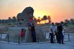 People stand near the Lion of Babylon at the archaeological site of Babylon, Iraq, Friday, July 5, 2019. Iraq on Friday celebrated the UNESCO World Heritage Committee's decision to name the historic city of Babylon a World Heritage Site in a vote held in Azerbaijan's capital, years after Baghdad began campaigning for the site to be added to the list. (AP Photo/Anmar Khalil)