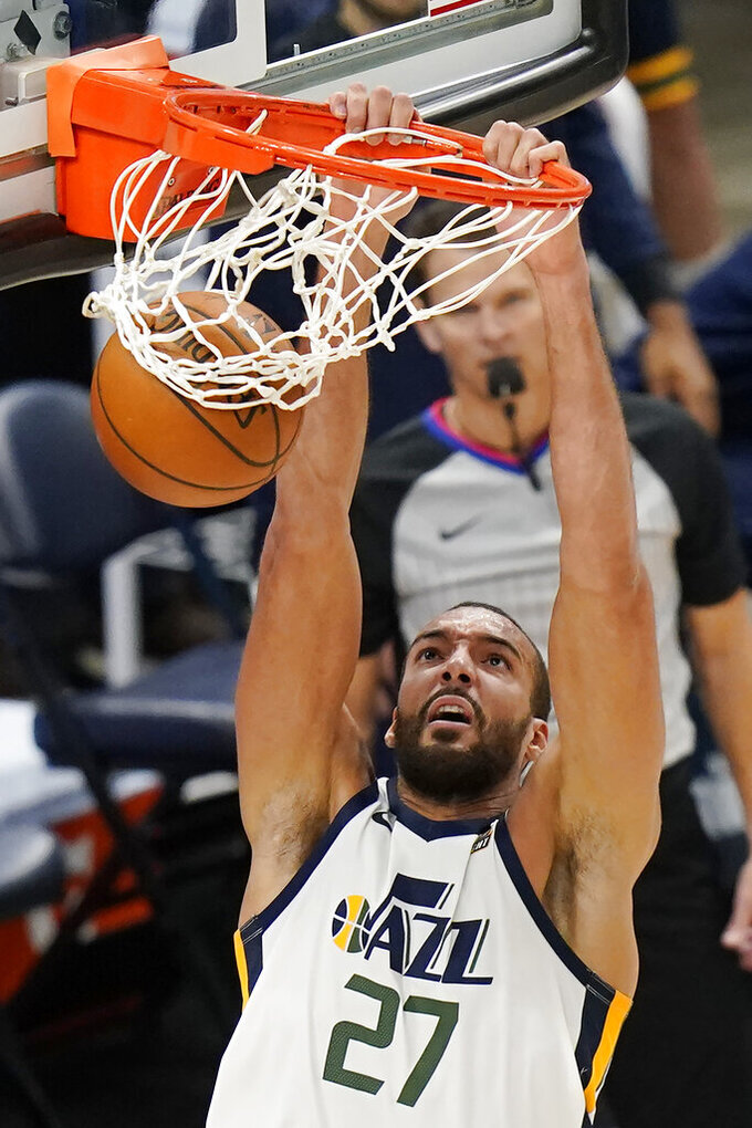 Utah Jazz center Rudy Gobert (27) dunks against the Phoenix Suns during the second half of an NBA preseason basketball game, Monday, Dec. 14, 2020, in Salt Lake City. (AP Photo/Rick Bowmer)