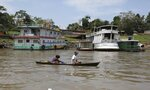 Local residents navigate the Amazon River in front of Tabatinga, Brazil, border with Peru and Colombia, Thursday, Sept. 5, 2019. Colombia's President Ivan Duque, Peru's President Martin Vizcarra, and Ecuador's President Lenin Moreno, will meet in Leticia, on their shared Amazon border, in a summit to announce joint measures that these countries will take to protect the Amazon. (AP Photo/Fernando Vergara)