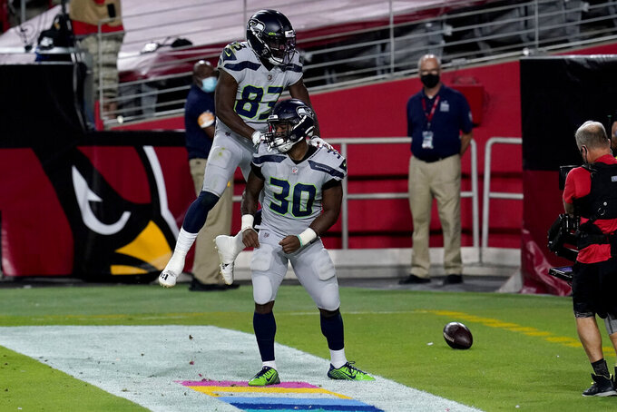 Seattle Seahawks running back Carlos Hyde (30) celebrates his touchdown with teammate David Moore (83) during the first half of an NFL football game against the Arizona Cardinals, Sunday, Oct. 25, 2020, in Glendale, Ariz. (AP Photo/Ross D. Franklin)