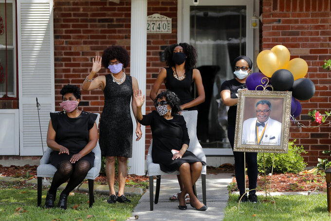 FILE - In this April 22, 2020, file photo, the family of Larry Hammond waves as a line of cars with friends and family who could not attend his funeral due to the coronavirus, pass by their home, in New Orleans. Hammond was Mardi Gras royalty, and would have had more than a thousand people marching behind his casket in second-line parades. (AP Photo/Gerald Herbert, File)