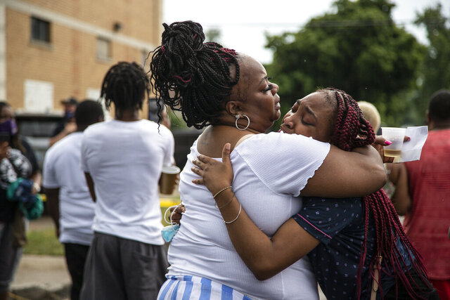 Kamya Gorden, right, is comforted by her mother, Pursha Gorden, following the fatal shooting of a man, Friday, July 10, 2020, who the city's police chief said fired at officers investigating a Fourth of July block party shooting, in Detroit. (Junfu Han/Detroit Free Press via AP)
