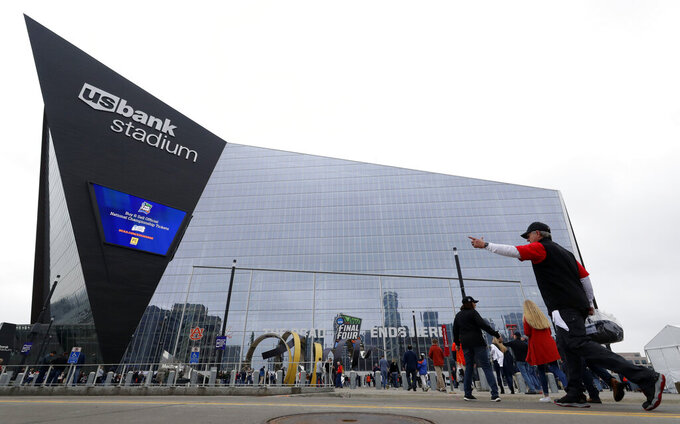 Fans arrive at U.S. Bank Stadium before the semifinals of the Final Four NCAA college basketball tournament, Saturday, April 6, 2019, in Minneapolis. (AP Photo/Matt York)