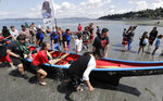 Members of the Cowlitz Indian Tribe pull their canoe onshore after receiving permission from the host Muckleshoot tribe during a stop on the annual tribal canoe journey through the Salish Sea Thursday, July 18, 2019, in Seattle. About 20 canoes from Northwest Native coastal tribes landed Thursday at Alki Beach on one of several legs of the canoe journey that gathers other canoe families from host tribes as they travel to a final landing, this year near Bellingham, Wash., at the Lummi Nation. (AP Photo/Elaine Thompson)