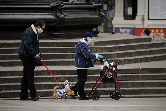 A woman wearing a home made face shield and mask walks a dog in Piccadilly Circus, central London, Sunday, May 3, 2020. The highly contagious COVID-19 coronavirus has impacted on nations around the globe, many imposing self isolation and exercising social distancing when people move from their homes. (AP Photo/Matt Dunham)