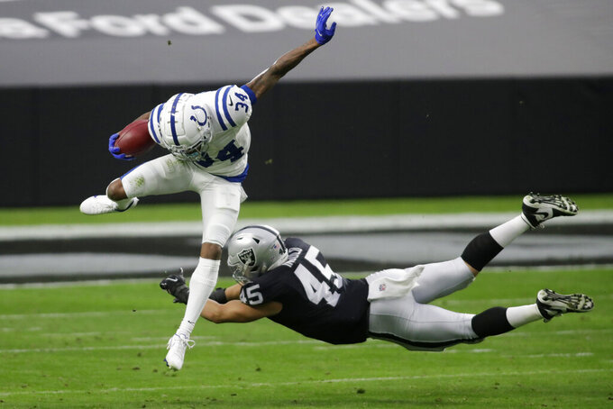 Indianapolis Colts cornerback Isaiah Rodgers (34) jumps over Las Vegas Raiders fullback Alec Ingold (45) during the first half of an NFL football game, Sunday, Dec. 13, 2020, in Las Vegas. (AP Photo/Isaac Brekken)