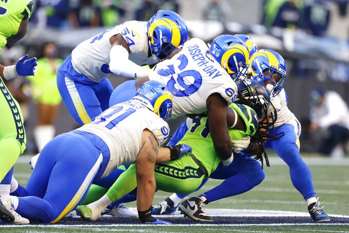 Seattle Seahawks running back Alex Collins is wrapped up by Los Angeles Rams defensive tackle Sebastian Joseph-Day (69) as he rushes during the first half of an NFL football game, Thursday, Oct. 7, 2021, in Seattle. (AP Photo/Craig Mitchelldyer)