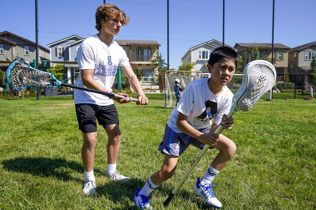 Zach Appel, right, Acalanes High School Varsity Lacrosse player, coaches 11-year-old Noah Shacklford on Tuesday, July 28, 2020 in Orinda, Calif. Zach and his friend Owen Estee have launched Lacrosse Against Hunger, to offer lacrosse coaching sessions to 7-14 year olds in exchange for a charitable donation to White Pony Express. All money raised goes directly to White Pony Express through Lacrosse Against Hunger's GoFundMe page. (AP Photo/Tony Avelar)