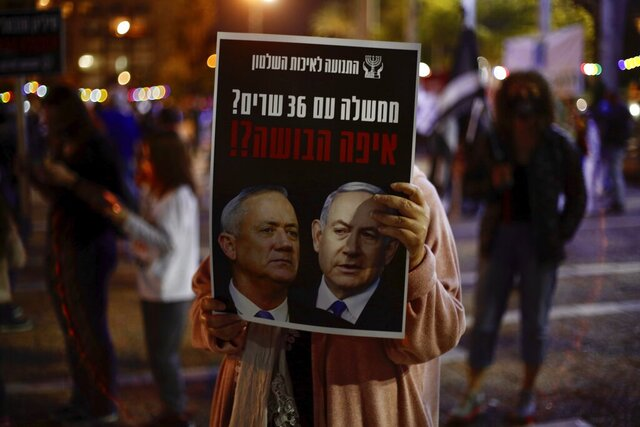 FILE - In this Saturday, May 2, 2020 file photo, a woman holds a poster of Israeli Prime Minister Benjamin Netanyahu, right, and Benny Gantz, that reads,