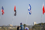 A man wearing a face mask against the coronavirus drives past flags, from left, of the United States, United Arab Emirates, Israel and Bahrain at the Peace Bridge in Netanya, Israel, Monday, Sept. 14, 2020. For the first time in more than a quarter-century, a U.S. president will host a signing ceremony between Israelis and Arabs at the White House, billing it as an