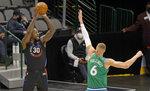 New York Knicks forward Julius Randle (30) attempts a 3-point shot against Dallas Mavericks center Kristaps Porzingis (6) during the first half of an NBA basketball game Friday, April 16, 2021, in Dallas. (AP Photo/Ron Jenkins)