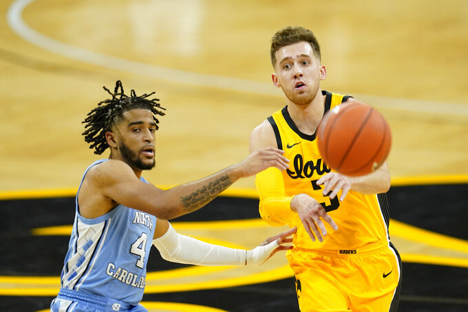 Iowa guard Jordan Bohannon passes ahead of North Carolina guard R.J. Davis, left, during the first half of an NCAA college basketball game, Tuesday, Dec. 8, 2020, in Iowa City, Iowa. (AP Photo/Charlie Neibergall)
