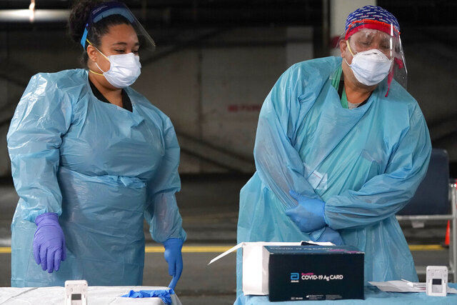 Nurses check on the status of rapid COVID-19 tests at a drive-through testing site in a parking garage in West Nyack, N.Y., Monday, Nov. 30, 2020. The site was only open to students and staff of Rockland County schools in an effort to test enough people to keep the schools open for in-person learning. (AP Photo/Seth Wenig)