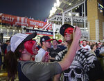 FILE - Cleveland Indians fan Leah Krankowski, left, paints the face of Chris Diz during a watch party for Game 7 of the baseball World Series between the Indians and the Chicago Cubs, outside Progressive Field in Cleveland, in this Wednesday, Nov. 2, 2016, file photo. While moving forward with a plan to change their name, the Cleveland Indians said they will not permit fans inside Progressive Field wearing headdresses or inappropriate face paint. The team announced the new guidelines on Wednesday, March 31, 2021, in advance of Monday's home opener against Detroit. (AP Photo/David Dermer, File)