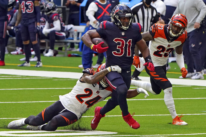 Houston Texans running back David Johnson (31) runs for a first down before being tackled by Cincinnati Bengals strong safety Vonn Bell (24) during the second half of an NFL football game Sunday, Dec. 27, 2020, in Houston. (AP Photo/Eric Christian Smith)