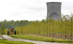 FILE - In this May 18, 2011, file photo, a worker drives a tractor through a tree farm in North Perry, Ohio, near the cooling towers of the Perry Nuclear Power Plant. A $60 million bribery case, involving ex-Ohio House Speaker Larry Householder and others, alleges to have helped prop up the Perry and Davis-Besse Nuclear Power Station in Oak Harbor, Ohio. The 2020 arrests of Householder and four associates in connection with the scheme have rocked politics and business across Ohio. (AP Photo/Amy Sancetta, File)