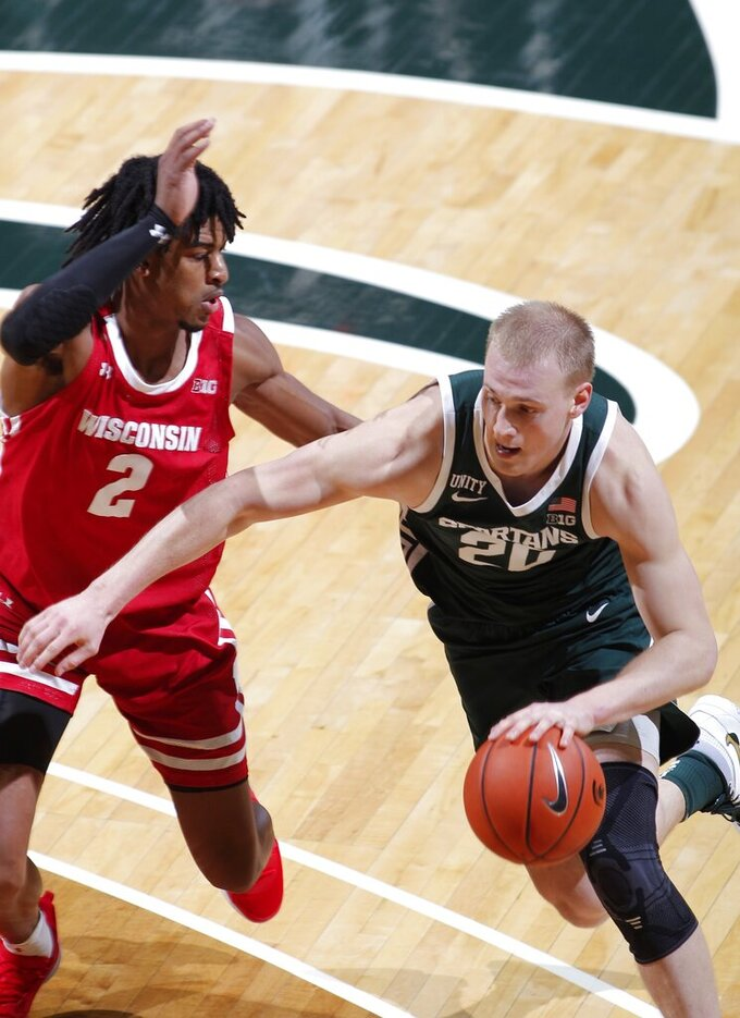 Michigan State's Joey Hauser, right, drives against Wisconsin's Aleem Ford (2) during the second half of an NCAA college basketball game, Friday, Dec. 25, 2020, in East Lansing, Mich. Wisconsin won 85-76. (AP Photo/Al Goldis)