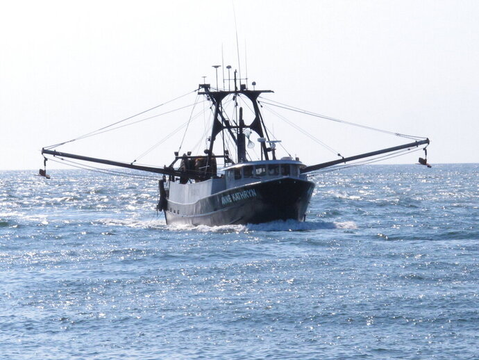 In this Sept. 11, 2019 photo, the commercial fishing boat Ann Kathryn sails into the Manasquan Inlet in Manasquan, N.J. Although they support effort to fight climate change and its impact on the world's oceans, the fishing industry fears it could be harmed by one of the promising solutions: the offshore wind energy industry. At a Congressional subcommittee hearing Monday Sept. 16, 2019 in New Jersey, fishermen asked for a seat at the table when important wind energy decisions are made, including where projects are located. (AP Photo/Wayne Parry)