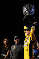 Kyle Busch, right, holds up his trophy in Victory Lane after winning a NASCAR Cup Series auto racing season championship at Homestead-Miami Speedway in Homestead, Fla., Sunday, Nov. 17, 2019.(AP Photo/Luis M. Alvarez)