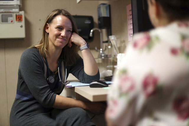 In this Nov. 7, 2019 photo, Dr. Angela Gatzke-Plamann is seen at the Necedah Family Medical Center in Necedah, Wis., doing a check-in with Catina Stoflet, who has been on medication-assisted treatment for seven months.