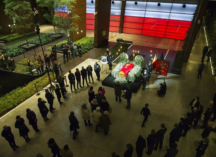 Mayor Pawel Adamowicz's coffin lies in state in the European Solidarity Centre in Gdansk, Poland, Thursday, Jan. 17, 2019. Residents of a Polish city are paying respects at the coffin of the longtime mayor who was killed in a stabbing attack. Gdansk Mayor Pawel Adamowicz will lie in state until Friday at a museum is devoted to the history of Poland's anti-communist Solidarity movement, which started in the city. (AP Photo/Wojciech Strozyk)