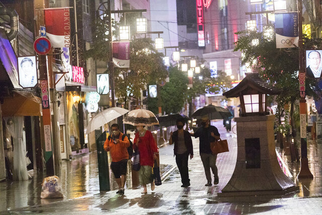 People walk on a street filled with bars, restaurants and other businesses in Tokyo on Friday, Oct. 9, 2020. A slow-moving typhoon off Japan's southern coast has triggered gusts and rain across a large part of the country and could bring heavy rains to the Tokyo region through early next week, though it was not expected to make landfall, officials said Friday. (AP Photo/Hiro Komae)
