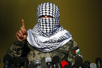 A masked Palestinian militant talks during a military drill organized by military factions outside Gaza City, Tuesday, Dec. 29, 2020. Palestinian militants in the Gaza Strip fired a salvo of rockets into the Mediterranean Sea on Tuesday as part of a self-styled military drill aimed at preparing for a possible war with Israel. (AP Photo/Adel Hana)