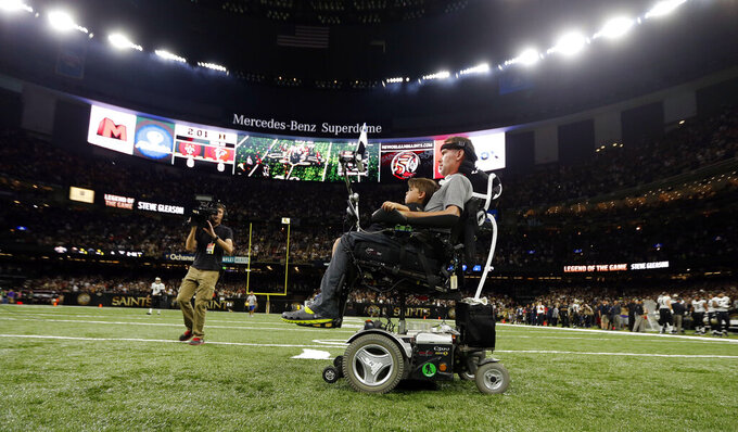 FILE - In this Sept. 26, 2016, file photo, former New Orleans Saints player Steve Gleason rides onto the field with with his son Rivers before an NFL football game against the Atlanta Falcons in New Orleans. He's the Saints' biggest fan and the perfect symbol of a city that knows a thing or two about overcoming hardship. As the Big Easy goes for another championship, Gleason is along for the ride. Even though his body failed him, perhaps because of the game he loved so much, he never lost the will to live and love and make a difference. (AP Photo/Gerald Herbert, File)