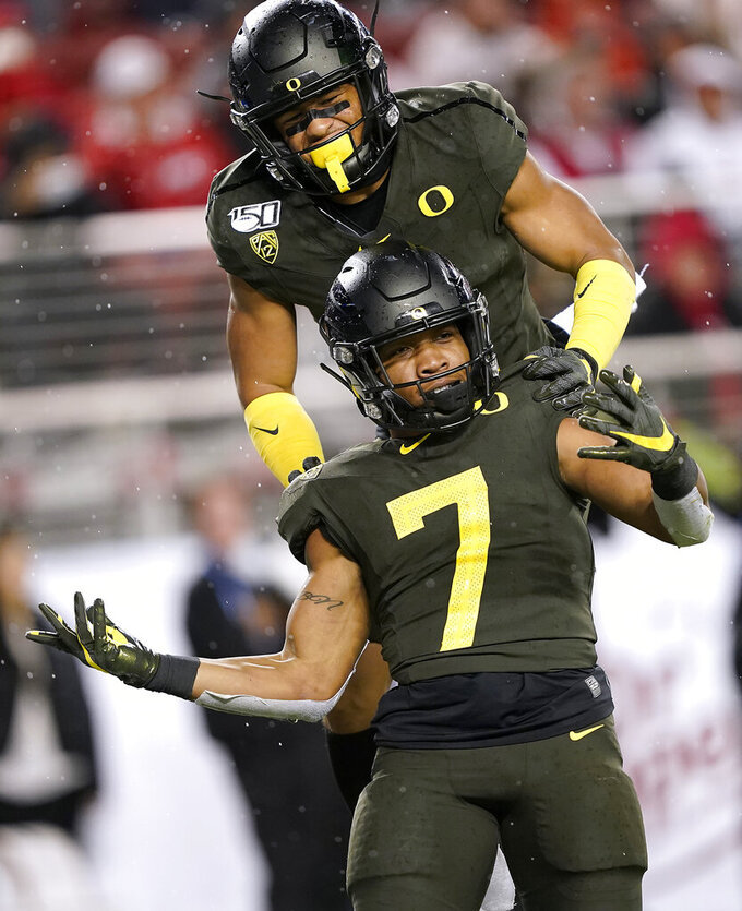 Oregon running back CJ Verdell (7) celebrates with Johnny Johnson III, top, after scoring a touchdown against Utah during the second half of an NCAA college football game for the Pac-12 Conference championship in Santa Clara, Calif., Friday, Dec. 6, 2018. Oregon won 37-15. (AP Photo/Tony Avelar)