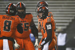 Oregon State quarterback Chance Nolan (10) celebrates his touchdown with Trevon Bradford (8), Keli'I Montibon (55) and Teagan Quitoriano (84) during the second half of the team's NCAA college football game against Oregon in Corvallis, Ore., Friday, Nov. 27, 2020. Oregon State won 41-38. (AP Photo/Amanda Loman)