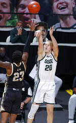 Michigan State's Joey Hauser, right, shoots a 3-pointer against Western Michigan's Greg Lee (23) during the second half of an NCAA college basketball game, Sunday, Dec. 6, 2020, in East Lansing, Mich. Michigan State won 79-61. (AP Photo/Al Goldis)